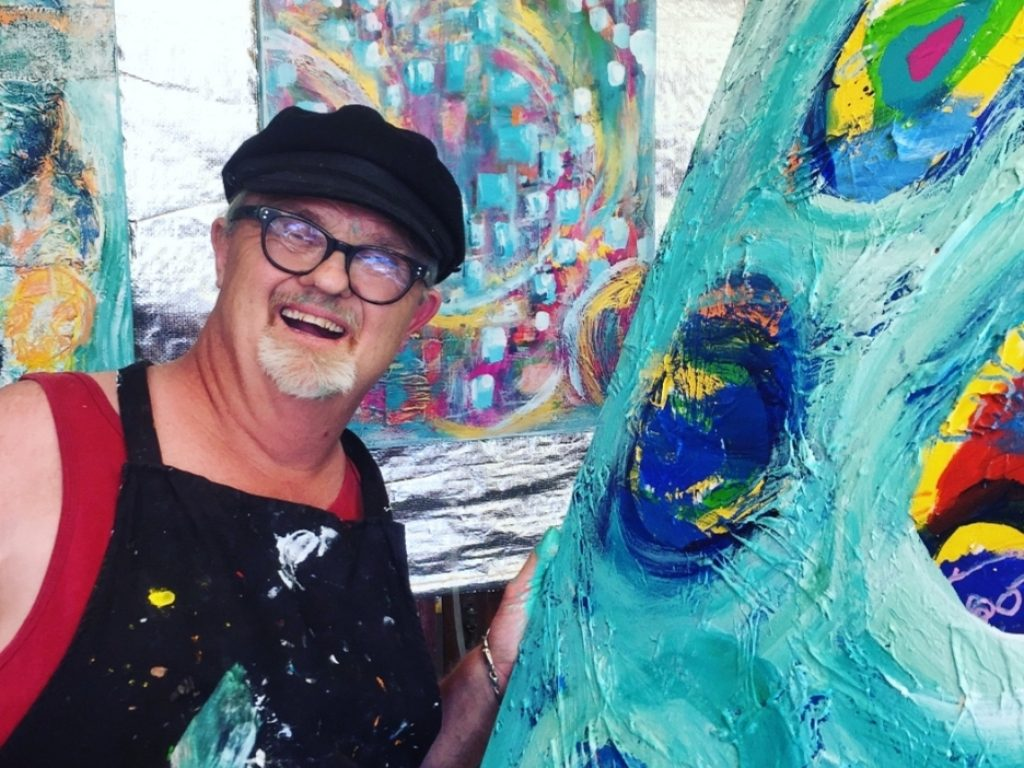 A man stands next to his colourful artwork