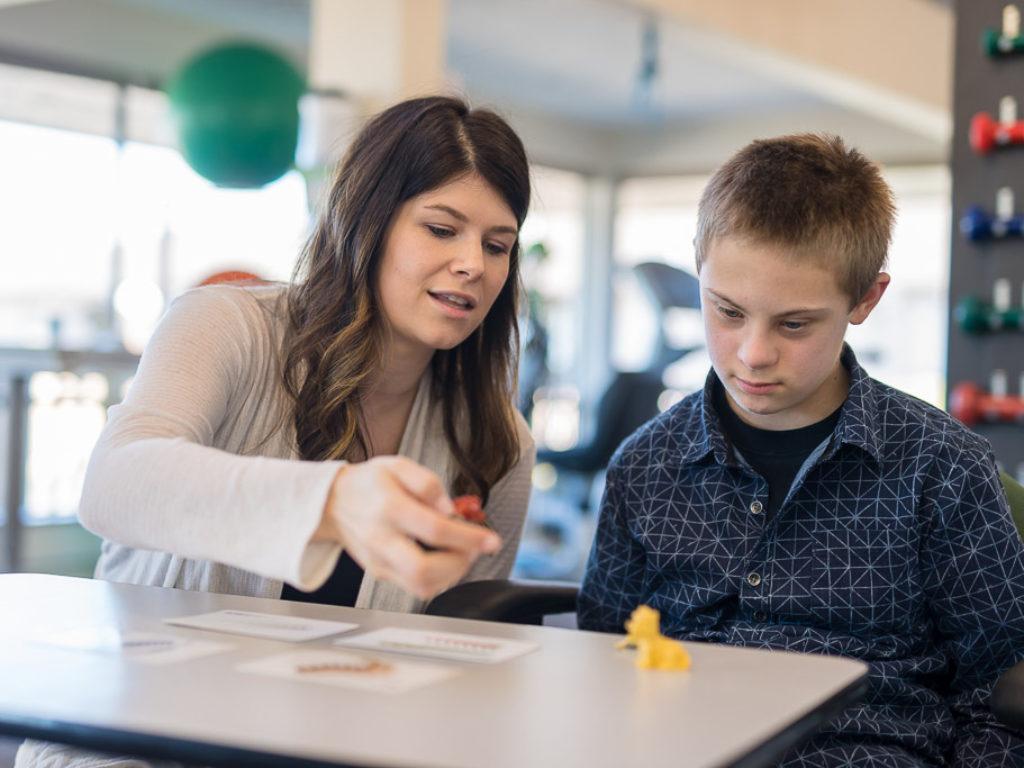 A woman teaching a school aged boy in a classroom