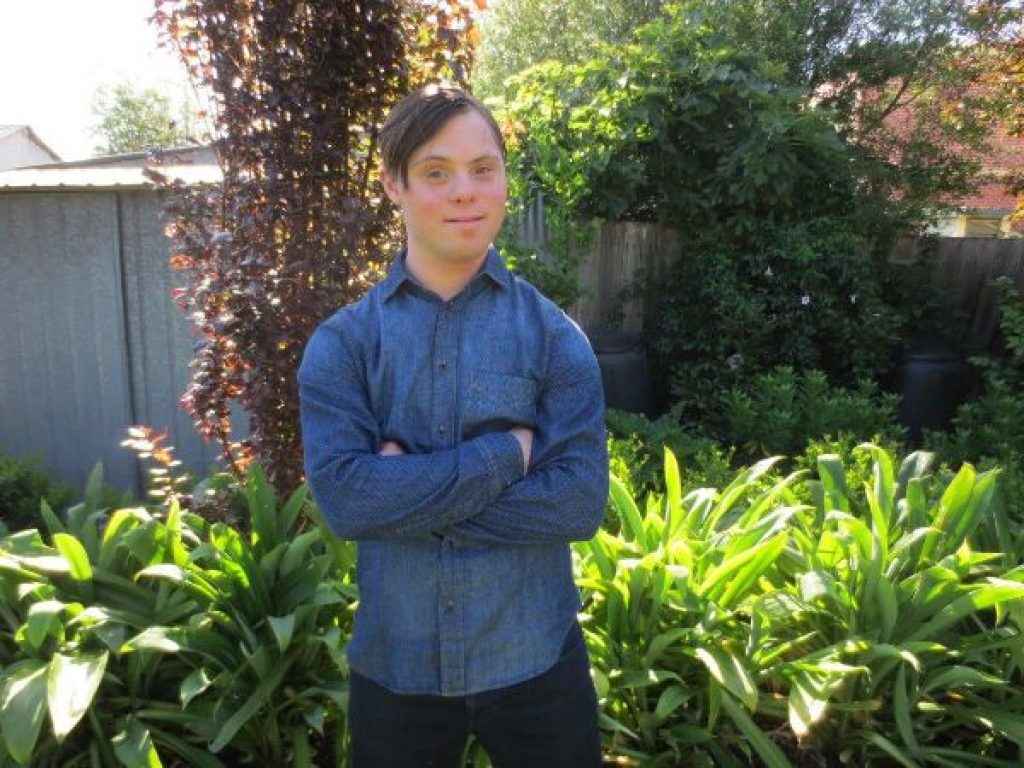 A young man stands outdoors in a garden in a blue shirt