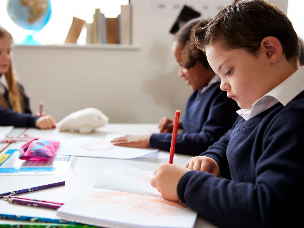 A young child sits at a desk in a classroom writing