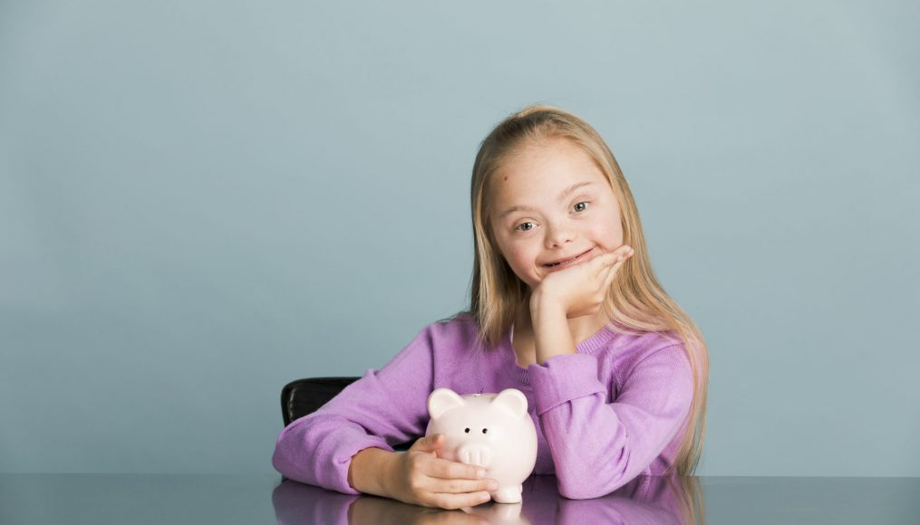A young blonde girl with Down syndrome is seated at a table smiling at the camera and holding a piggy bank.