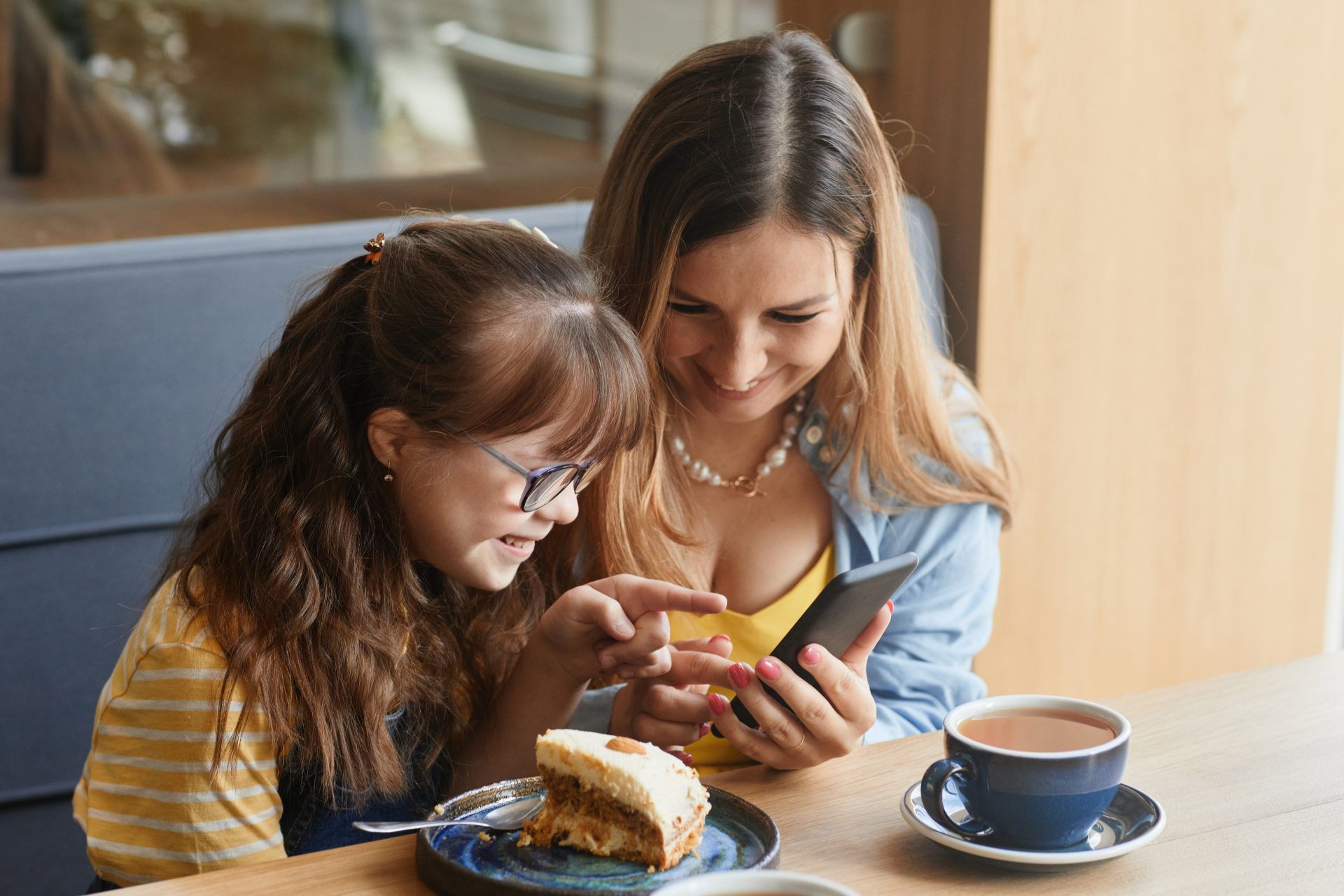 A woman and a young girl with Down syndrome are sitting in a cafe looking at a mobile phone screen together and smiling.