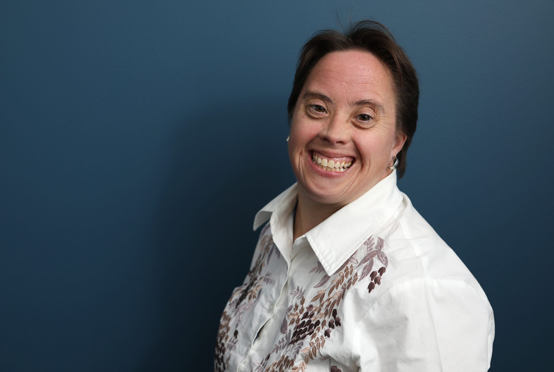 A woman with Down syndrome in a white collared shirt is smiling at the camera.