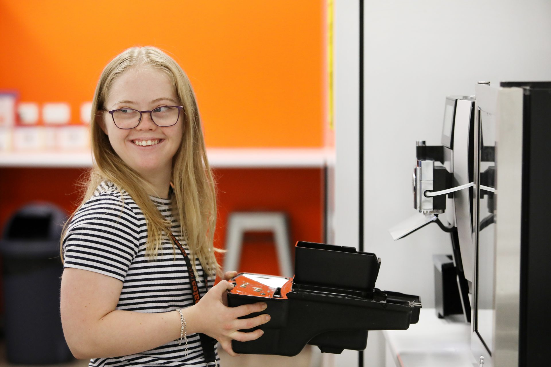 A young women with long blonde hair and glasses is cleaning a coffee machine in an office kitchen. She is smiling and looking out of the frame.