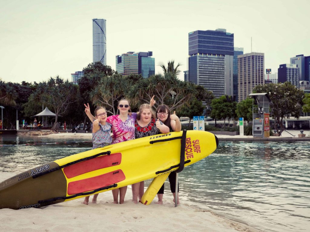 A group of girls behind a surf rescue surf board.