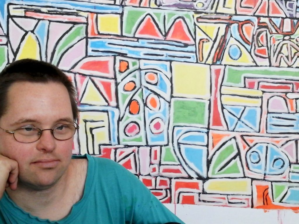 Alex Rees in front of his painting.
