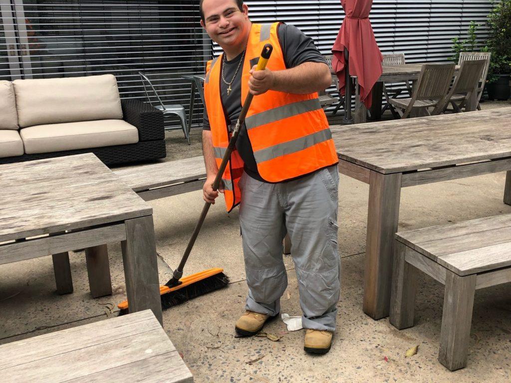 Man in orange vest sweeping the floor.