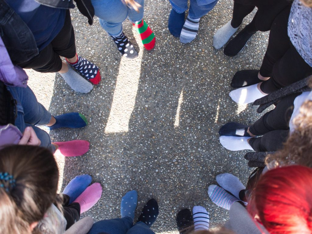 Several people standing in a circle wearing socks.