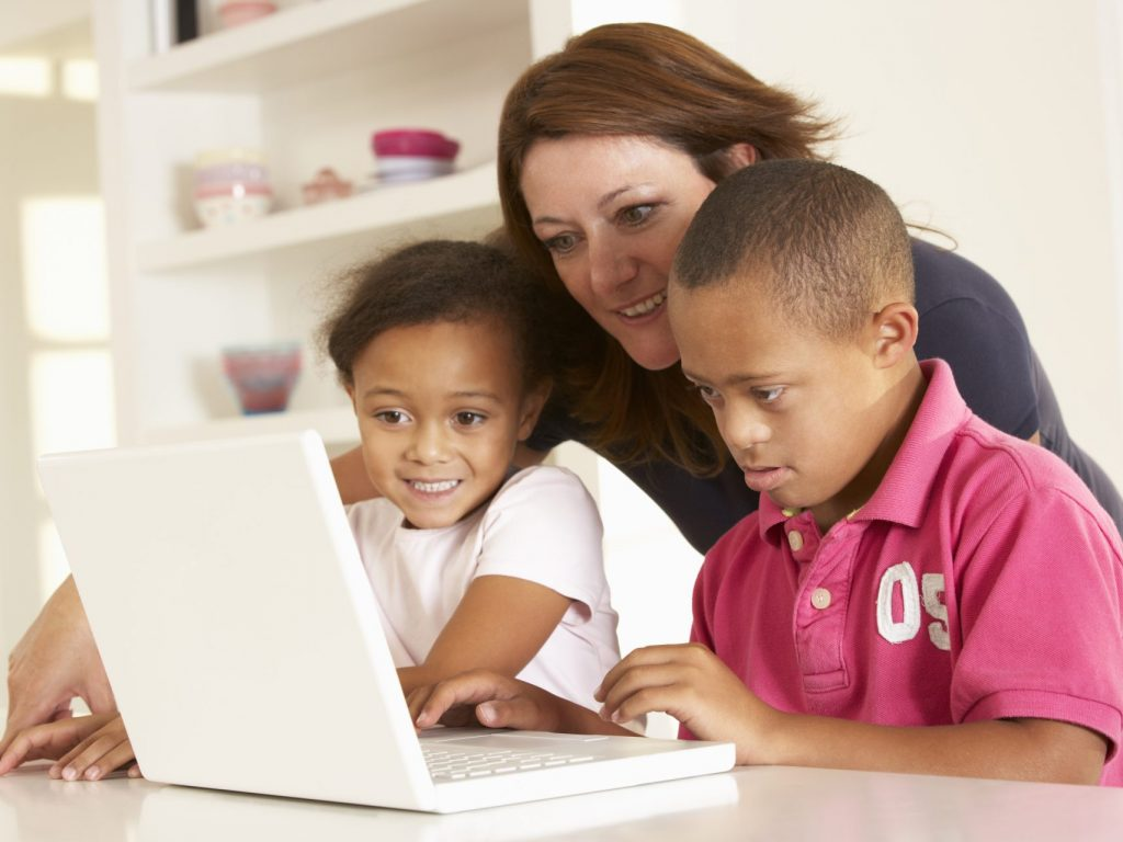 2 children and an adult using a computer.
