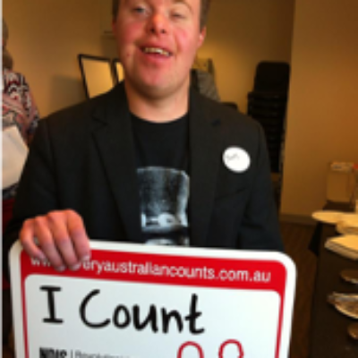 A young man holds a sign saying I count