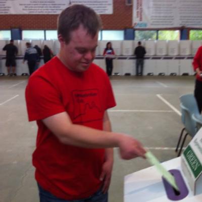 A man places a voting paper into a box