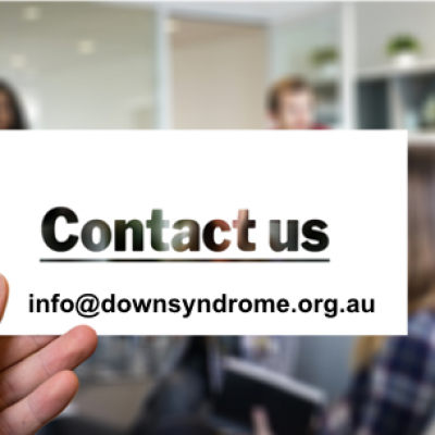 A hand holds a card with the email address info@downsyndrome.org.au