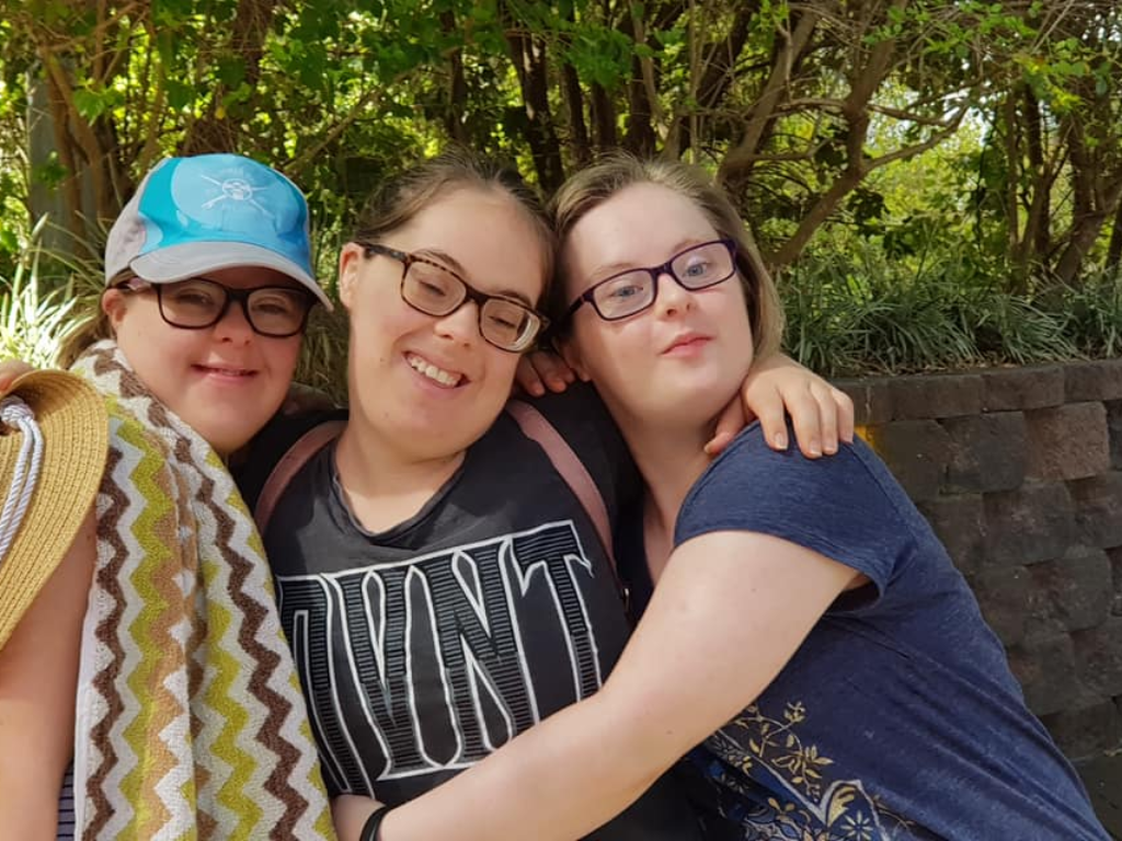Three young women with Down syndrome stand together outdoors