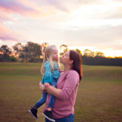 A mother holds a young daughter outdoors at sunset