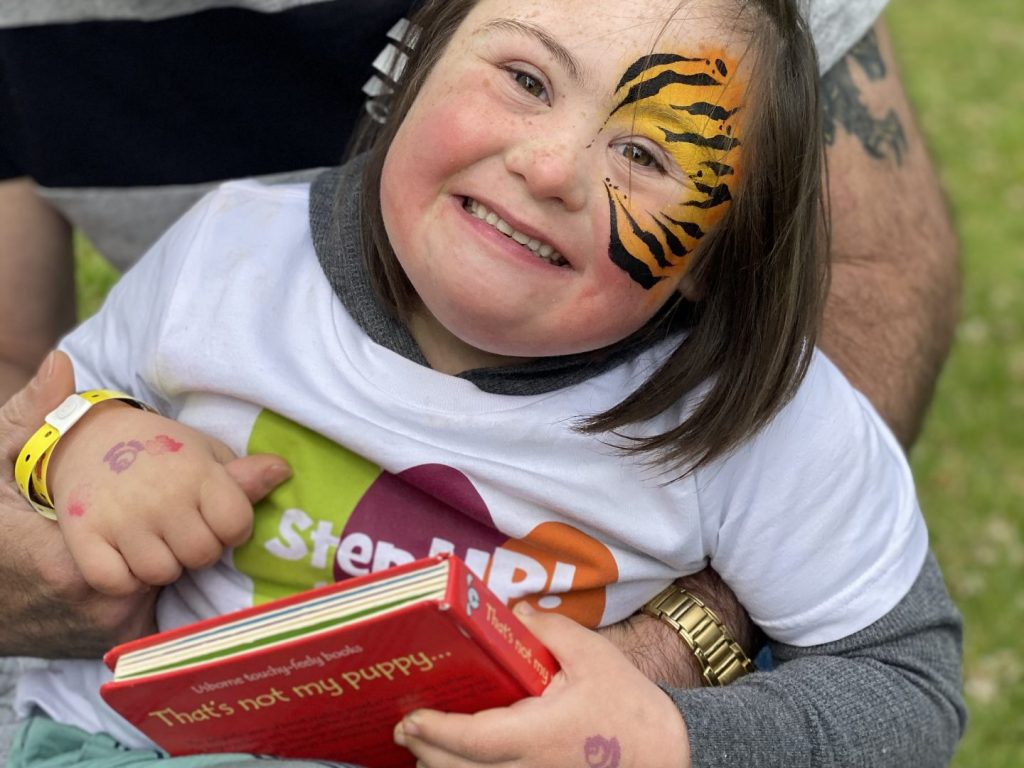A young girl at a fundraising event has a face painting and is holding hands with an adult