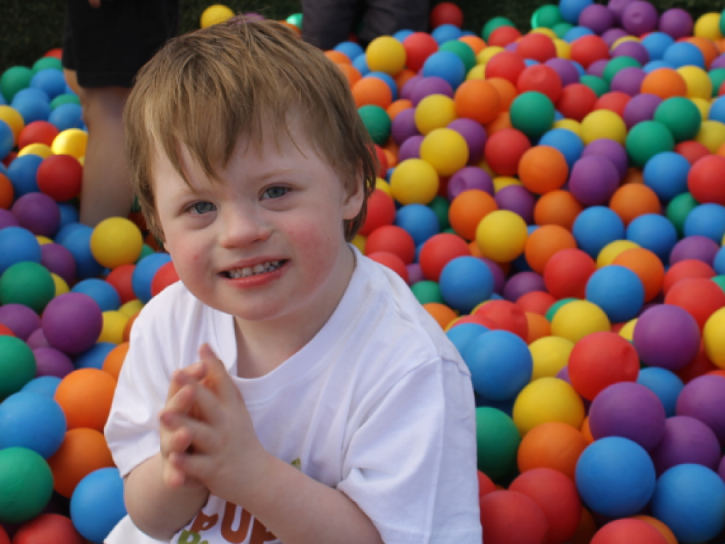 A young child plays with colourful balls