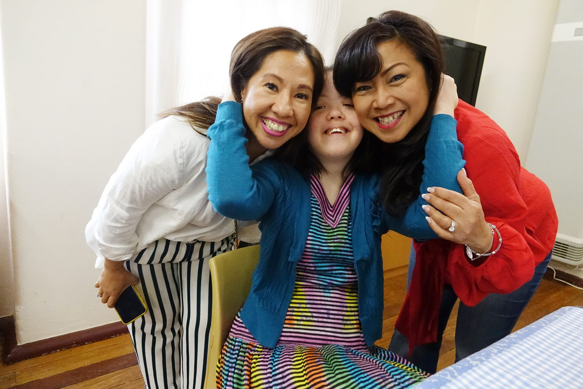 A young woman in a blue jumper is hugging two other women either side of her. They are all smiling and facing the camera.