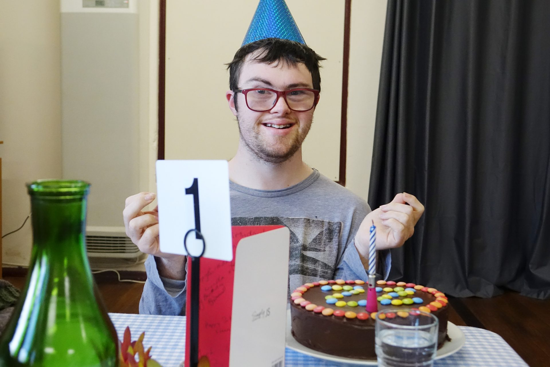 A young man wearing glasses and a blue birthday hat smiles at the camera. There is a chocolate cake in front of him with one candle on top.