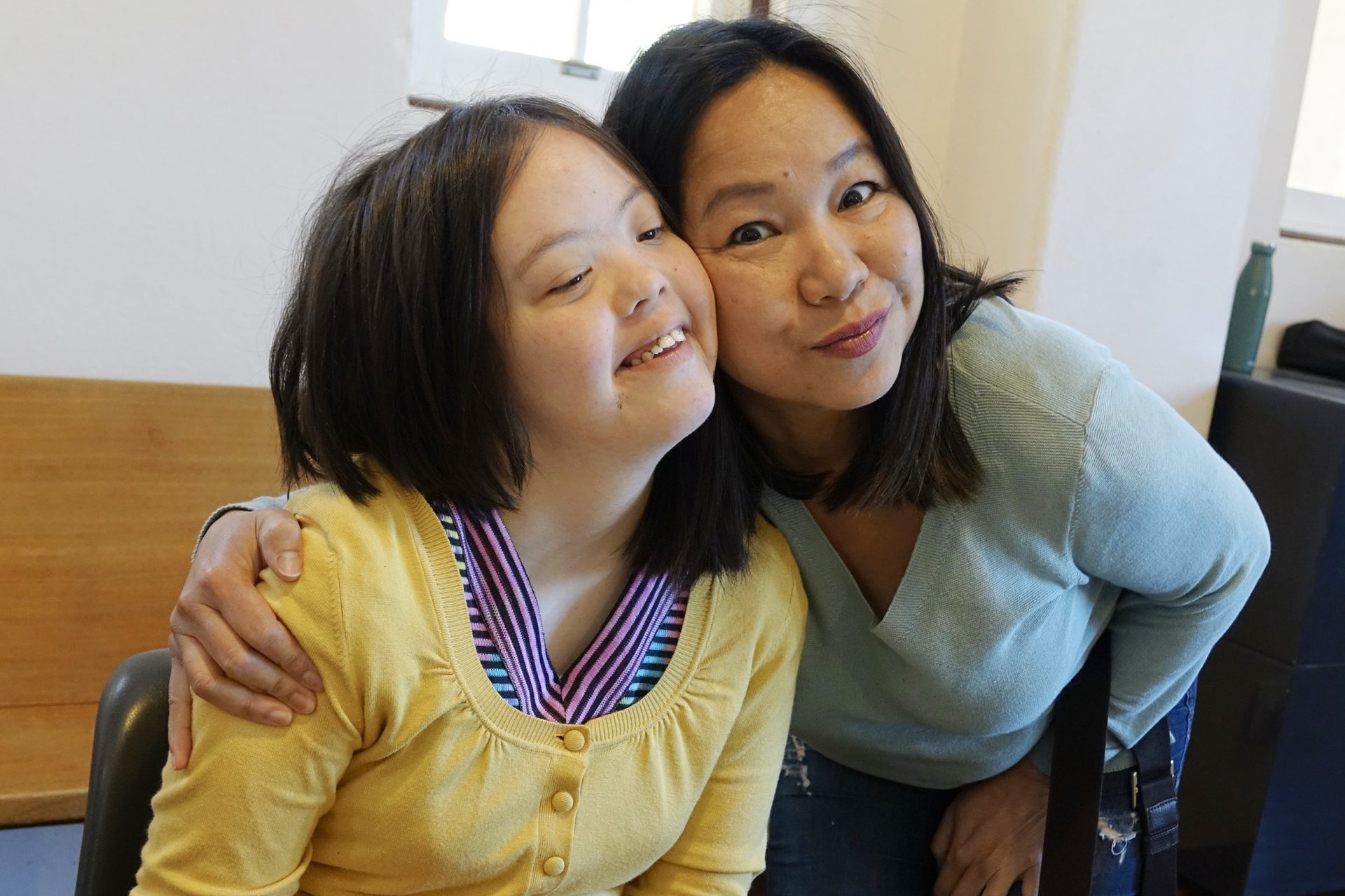 A young girl with dark hair and a yellow jumper is hugged by her mum. They are both smiling.
