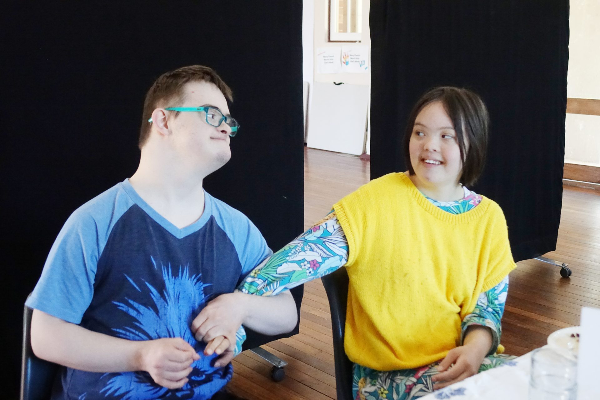 A young man in a blue shirt wearing glasses looks and smiles at a young woman on the right, who is wearing a yellow jumper and smiling. They are holding hands.