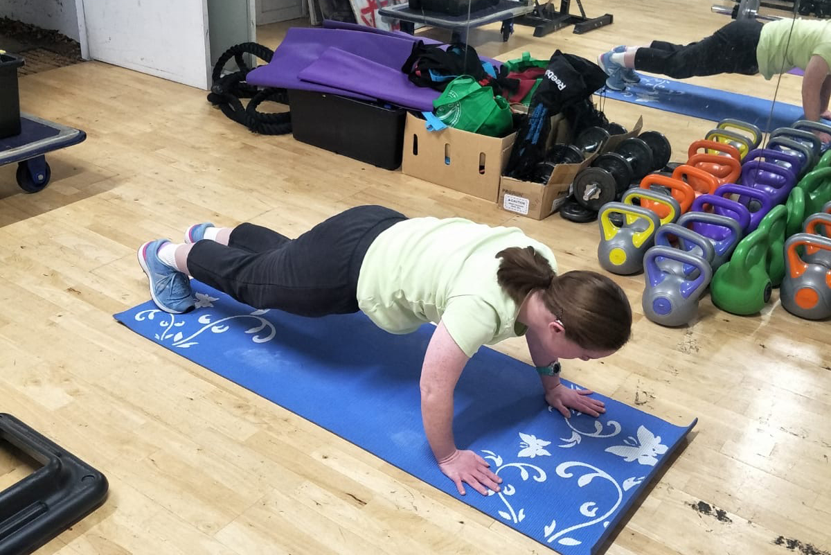 A young woman with Down Syndrome is in a gym holding the plank position on a blue mat.