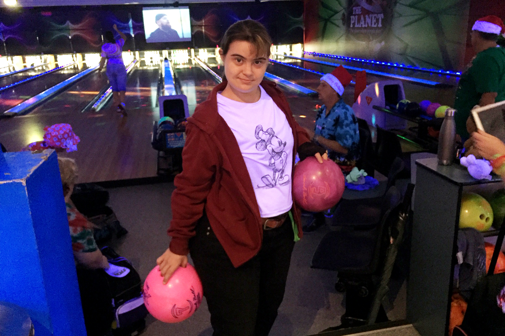 A woman with Down syndrome is in a bowling alley and holding two pink bowling balls.