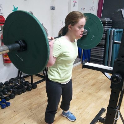 A young woman with Down Syndrome has a bar with heavy weights on her shoulders.