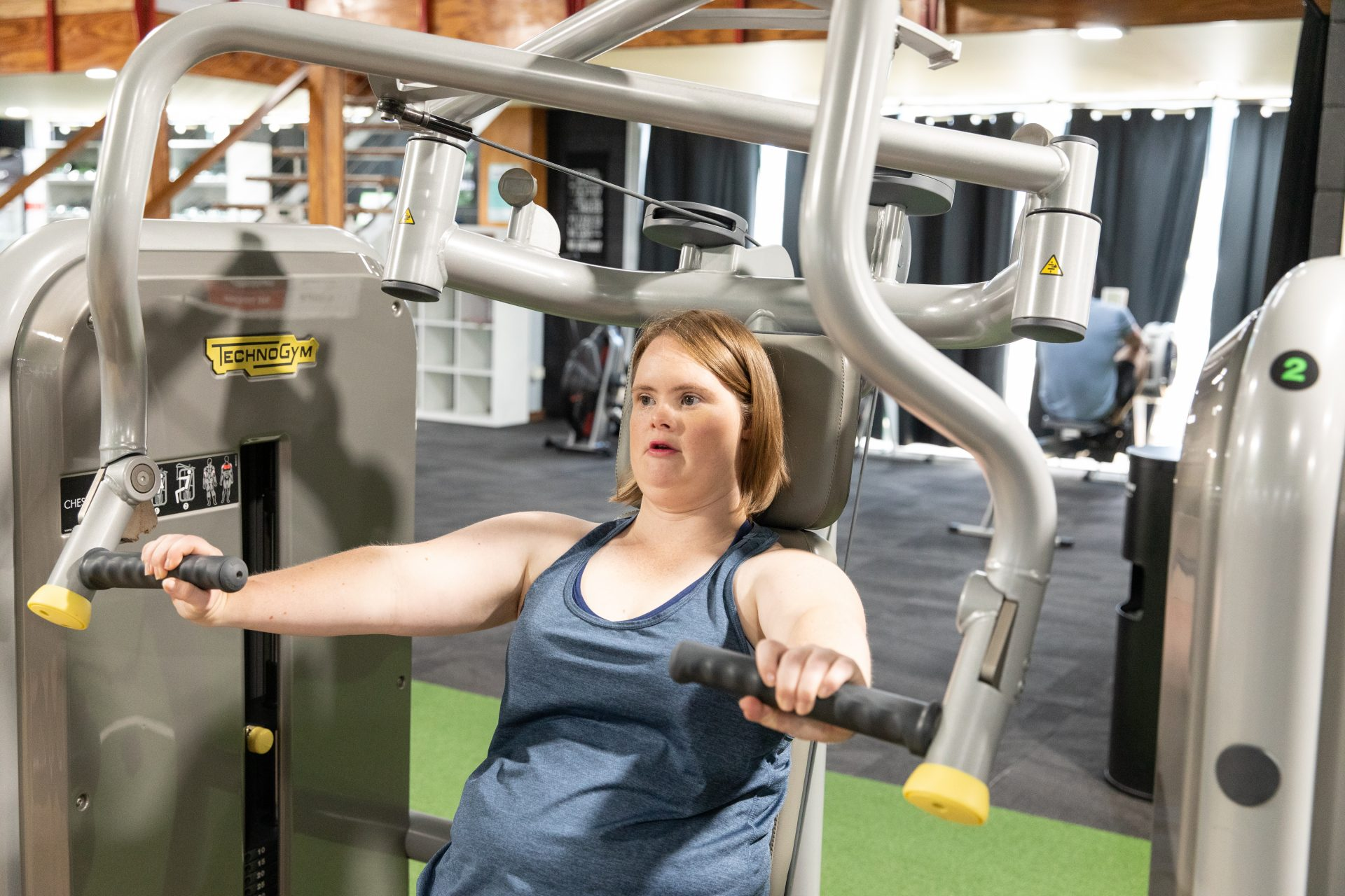 A young woman with Down syndrome uses gym equipment.