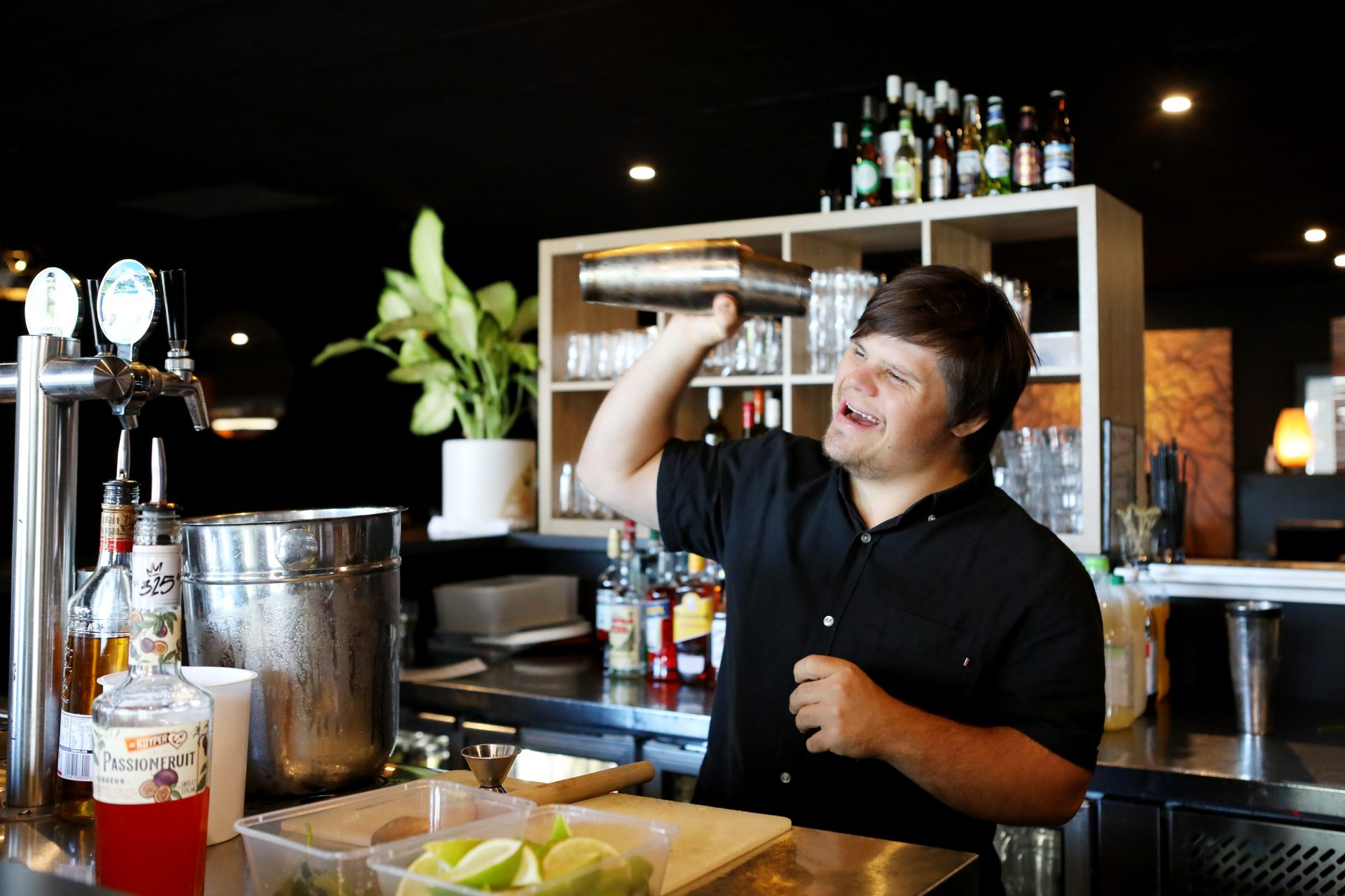 A man with Down syndrome is shaking a cocktail mixer behind a bar.