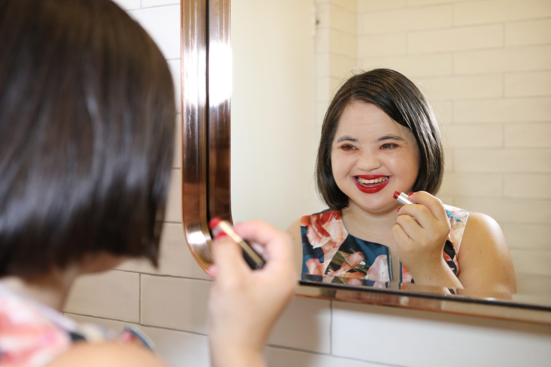 A young woman with brown hair looks into a mirror and puts on red lipstick