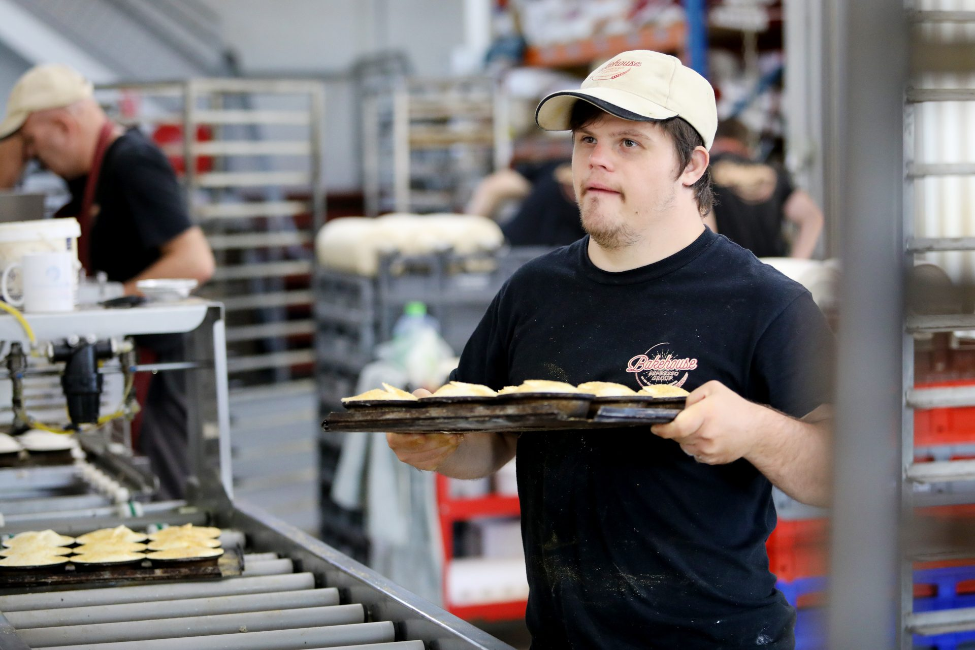 A man wearing a cap is moving a tray of pies in a bakehouse.