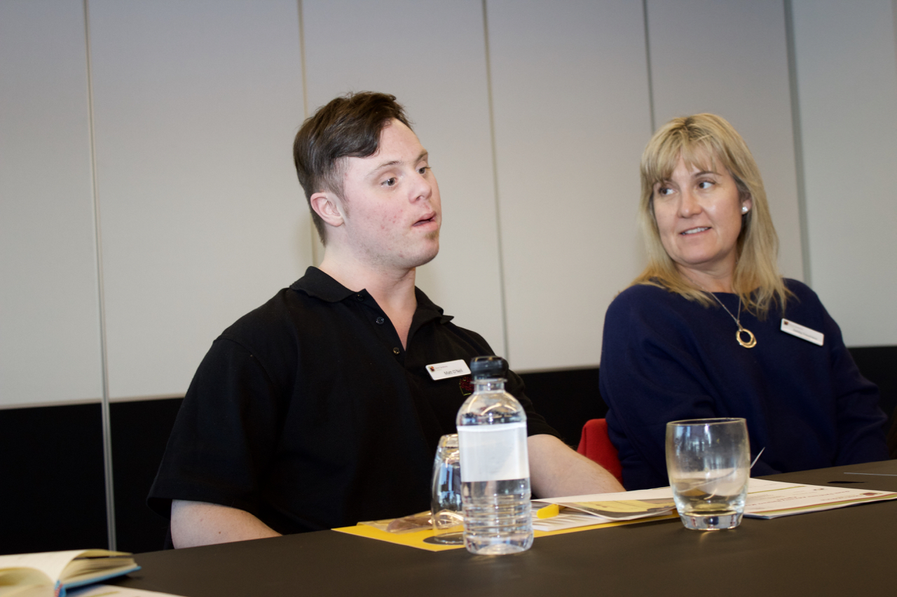 A man with Down syndrome sits at a table and is about to talk.