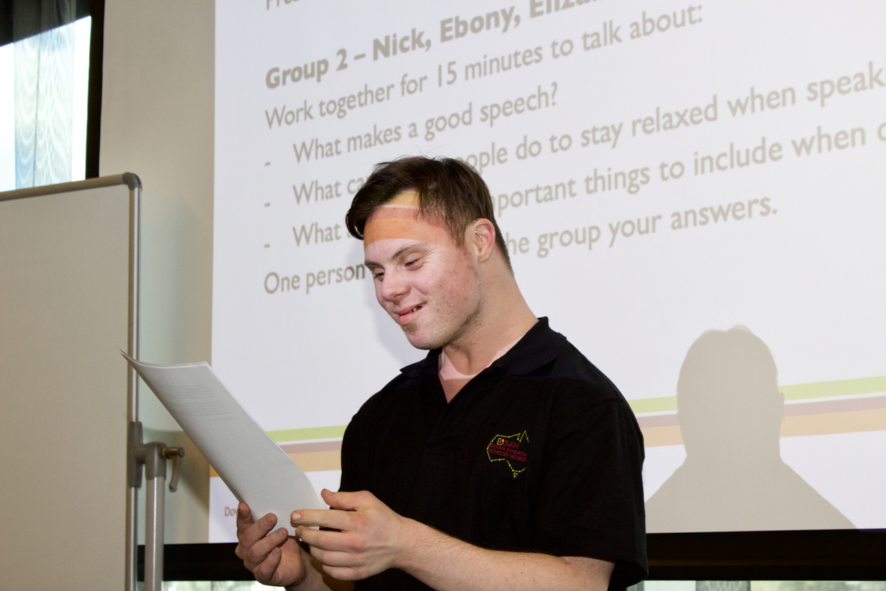 A man with Down syndrome standing in front of a presentation and looks at a sheet of paper.