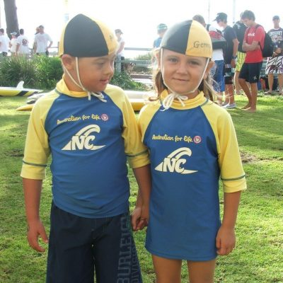 Aden Clarke as a young Nipper with his sister whoa re both dressed in blue and yellow outfits.