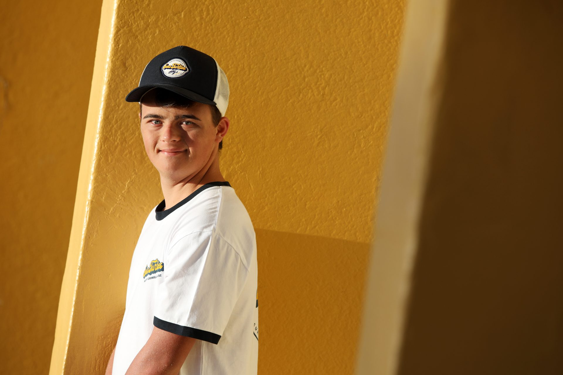 A young man with dark hair and a blue cap smiles at the camera.