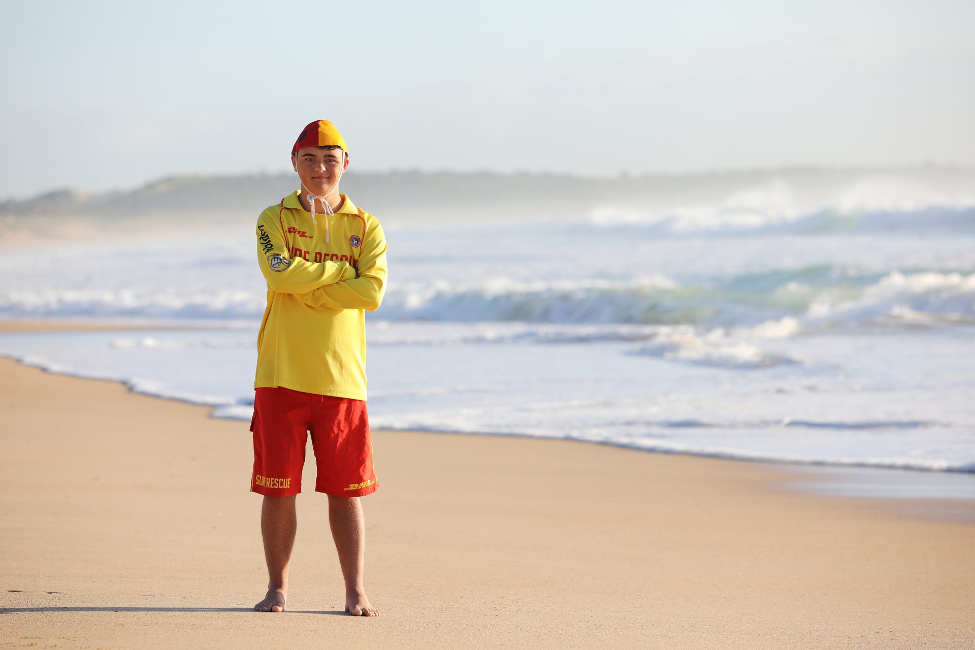 A young male surf life saver is standing on the beach in a yellow and red uniform. He is folding his arms and smiling at the camera.