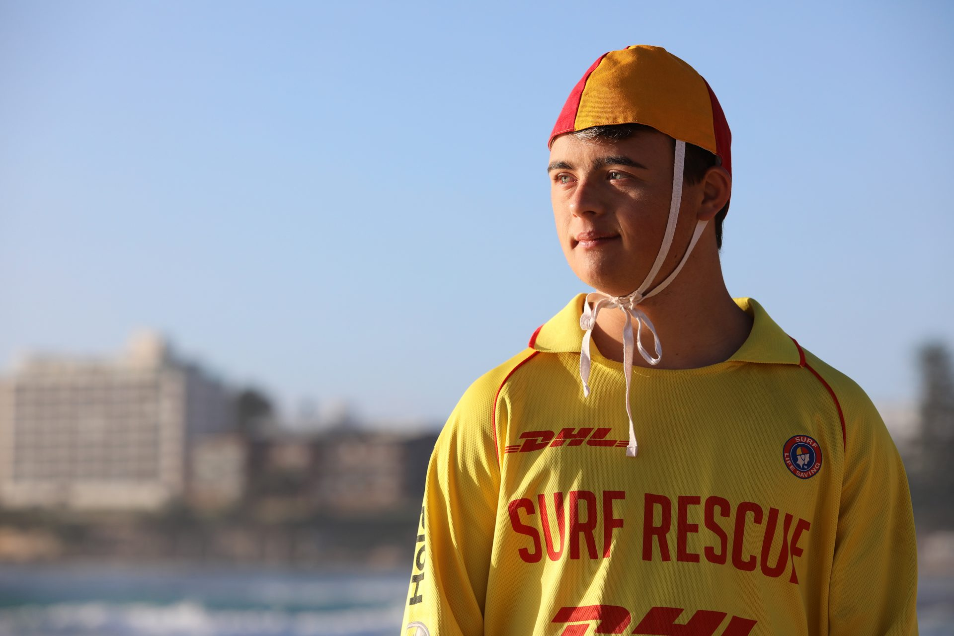 A young man dressed in a life saving outfit looks out to the ocean.
