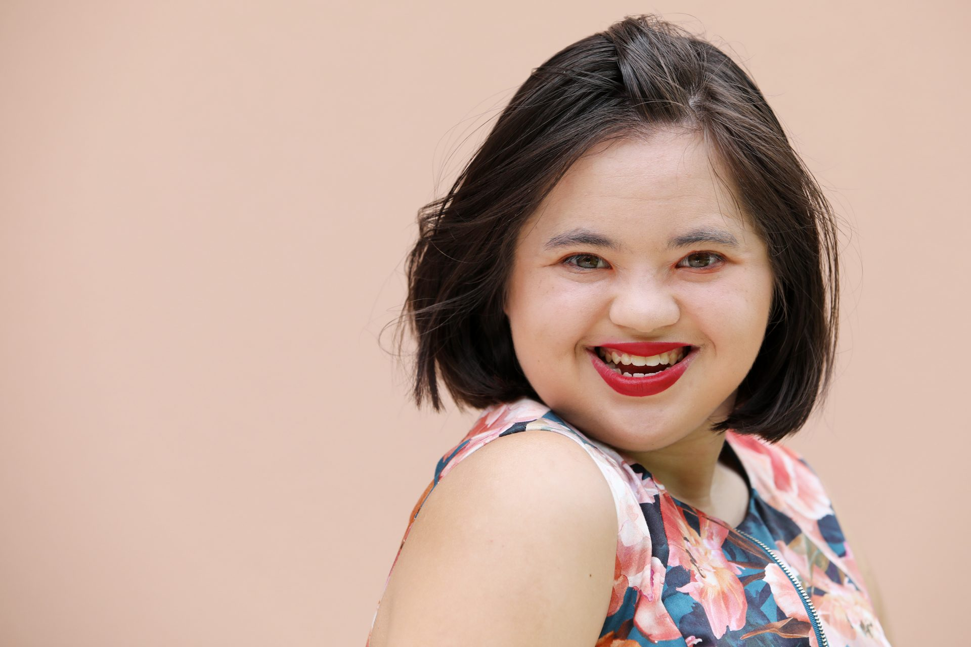 A young woman with Down syndrome who has short brown hair and red lipstick smiles at the camera.