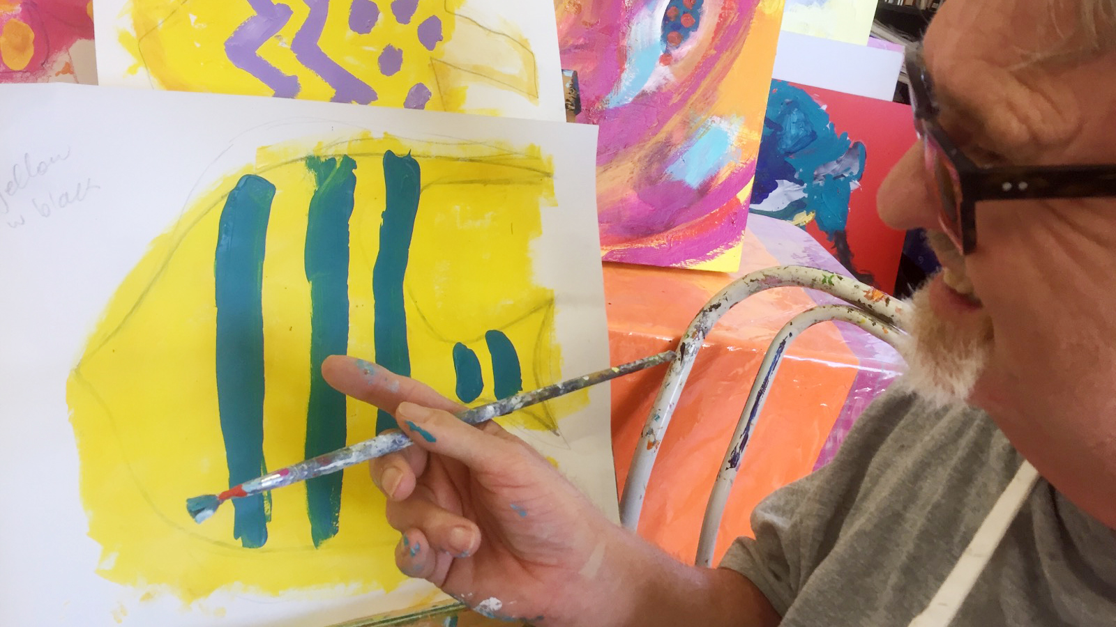 A man with a paint brush in his hand points at a painting of a yellow fish with blue stripes.