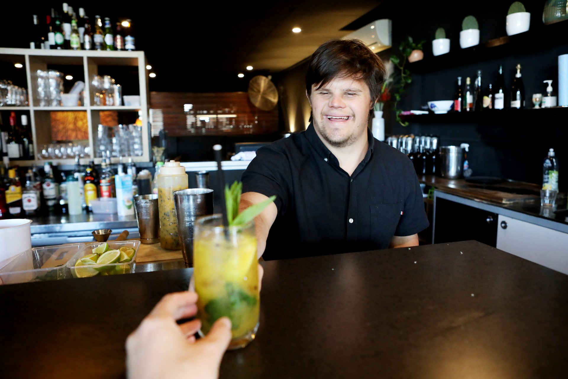 A man with Down syndrome serves a colourful cocktail to a bar patron.