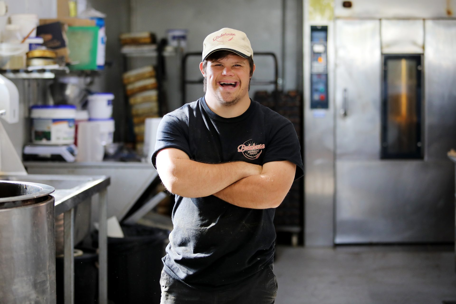 A young man with Down syndrome who is wearing a cap and folding his arms is smiling at the camera. He is standing in a bakery.