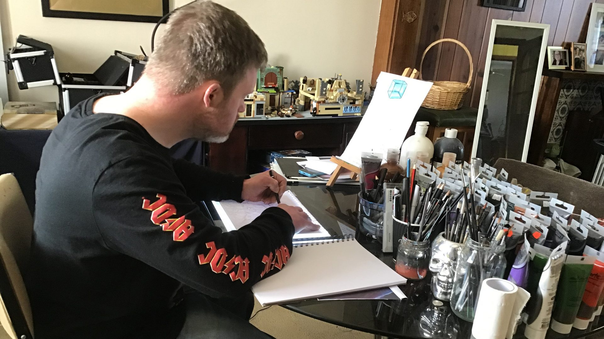 An artist is drawing in a sketch book at a desk.
