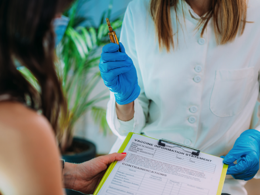 A health professional provides a clipboard with information about vaccines