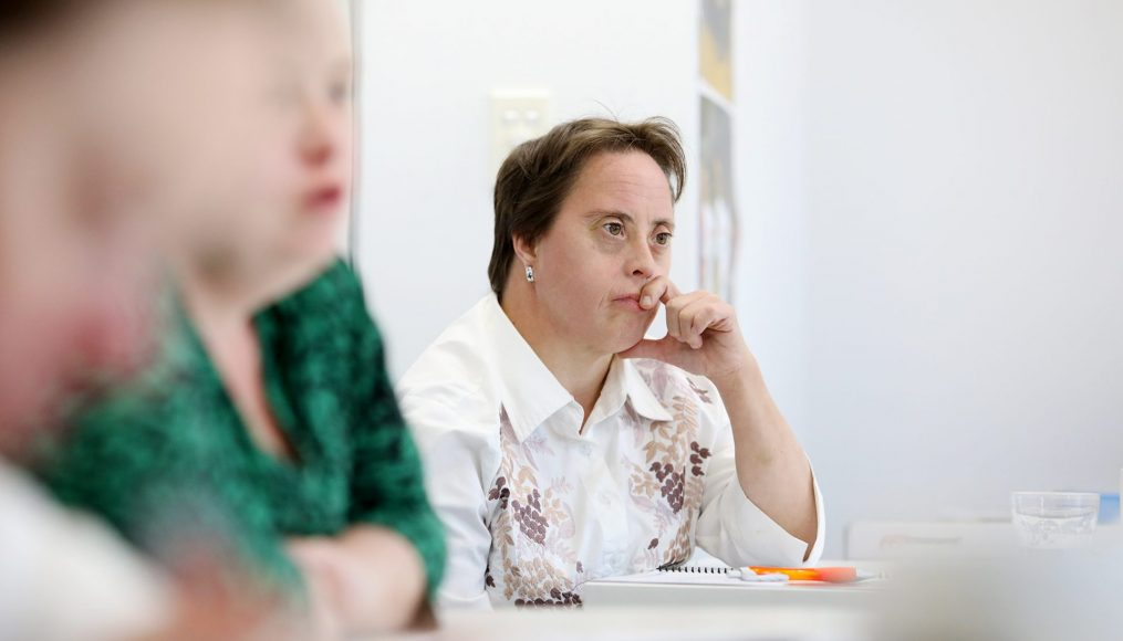 A woman with short dark hair is sitting at a desk with her elbow rested on the top as she listens to someone off to the right.